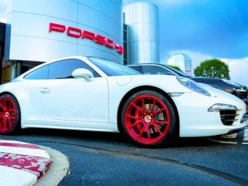Białe Porsche z krwistoczerwonym - Białe porsche 911 zaparkowane w pobliżu białego i szarego betonowego budynku w ciągu dnia. Fairf