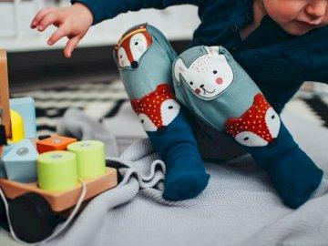 Toddler Toy Floor Riga - Baby boy wearing pair of blue socks. Riga, Latvia