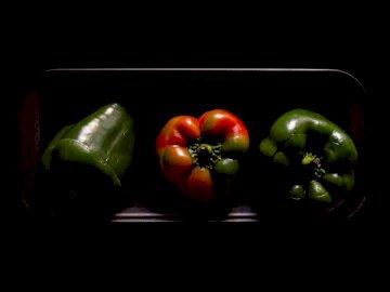 Pepper, food - Three orange and green bell peppers on black plate. São Paulo / Brazil