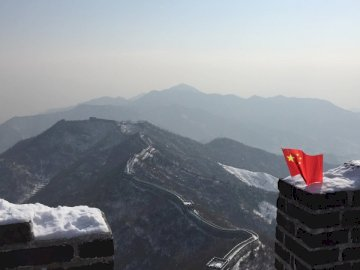 Great Wall of China in winter, - Aerial photography of a red flag on top of a stone wall. Atlanta