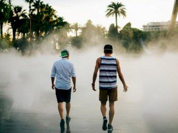 Auf dem Weg nach Nizza - Straßenfotografie von zwei Männern, die vor Wasserbrunnen gehen. Lübeck, Deutschland