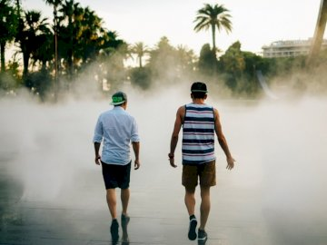 Walking Toward Nice - Street photography of two men walking in front of water fountain. Lübeck, Germany