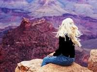 Grand Canyon - Kvinna som sitter på en brun klippa under dagen. NYC
