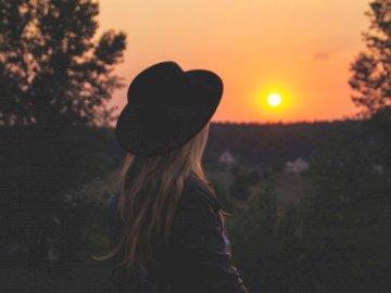 Ukraińska kobieta ogląda zachód słońca - Kobieta ubrana w czarny kapelusz, patrząc na zachód słońca. Ukraina