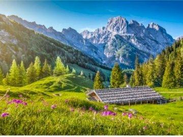 Krajobraz gór - piękne góry, mała drewniana chatka i zielona łąka