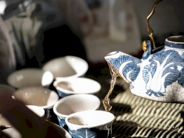 Hot Chinese tea from antique - White and blue ceramic teacup on brown woven table mat. Thailand