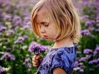 Lucy, dla dzieci - Dziewczynka gospodarstwa fioletowe kwiaty.