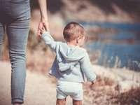 Rodzic i dziecko - Maluch chodzi nad brzegiem morza z osobą dorosłą. Francja