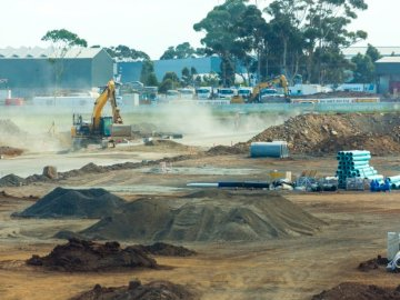 Roads construction at new - Yellow and blue helicopter on brown sand near body of water during daytime. Melbourne, Australia