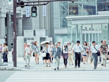 Crosswalk in Sapporo - People crossing pedestrian lane near building at daytime. Shanghai, China