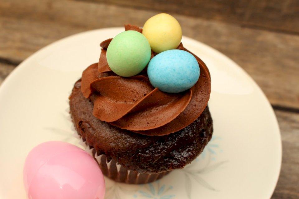 Ouă bomboane pe ciocolată - Tort de ciocolată cu ouă verzi și galbene pe o farfurie ceramică albă (10×10)