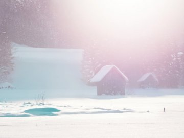 Two huts — - Black house on snow field at daytime. Austria