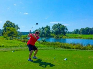 Huśtawki w czerwonej koszuli golfowej - Mężczyzna gra w golfa zdjęcie. Fairfax Virginia