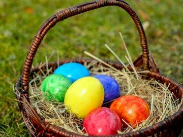 Wielkanoc - Pisanki wielkanocne w koszyczku z siankiem  na trawie. Pisanki wielkanocne w koszyczku wiklinowym. W