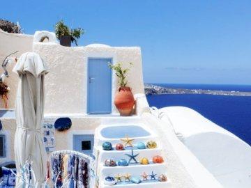 Morze Egejskie w Santorini, Grecja - Tradycyjny dom malowany na biało z widokiem na morze Egejskie w Santorini, Grecja