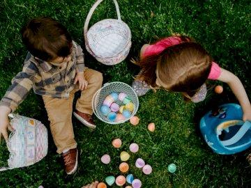Kinder teilen Ostereier - Mädchen in der grünen Jacke, die mit weißen und rosa Plastikkugeln auf grünem Grasfeld während