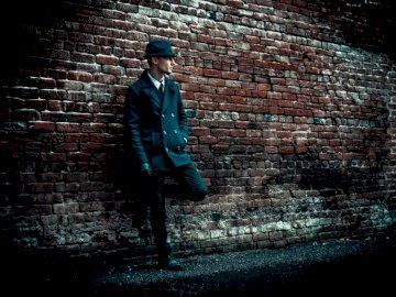 Modellierung für DIAMODSTIE - Mann trägt schwarzen Mantel, der auf braune Backsteinmauer stützt. pdx