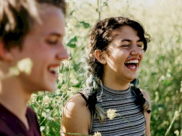 Friendly Humor - Man and woman laughing surrounded with green grass during daytime. Socal