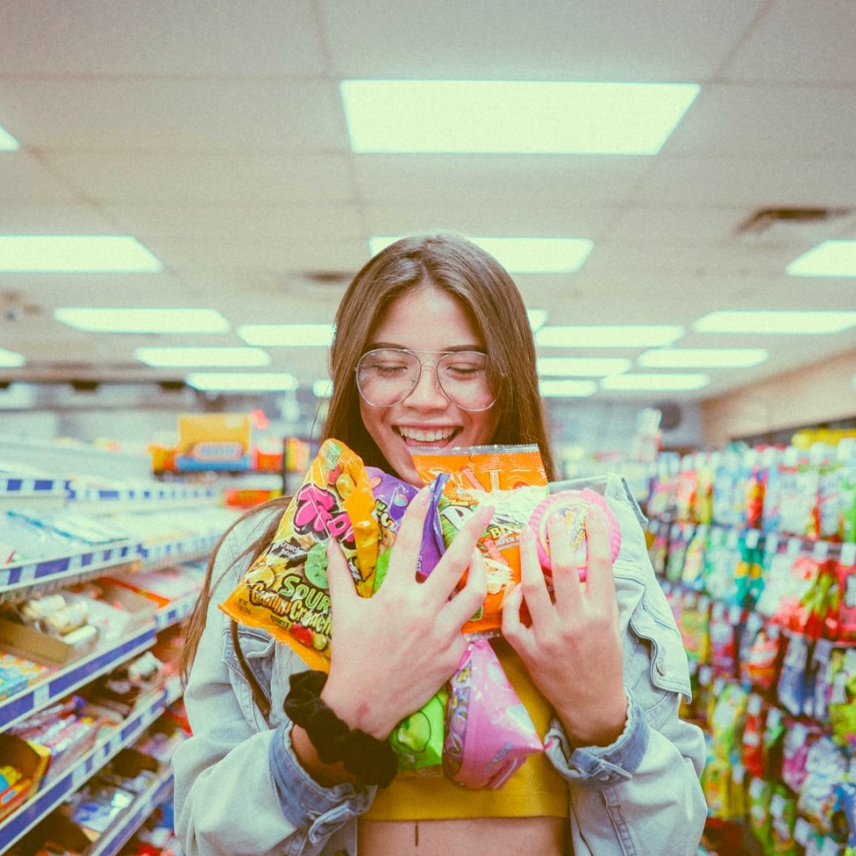 ?Princess Candy? - Smiling woman holding pack of food inside grocery store. Miami, Florida