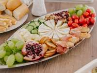 Starter, food - Sliced fruits on white ceramic plate. Ploiesti, Romania A wooden table topped with different types o
