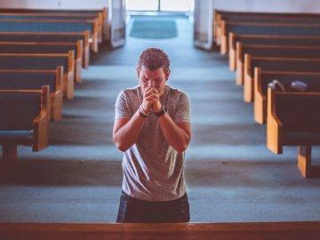 oração - Um homem rezando dentro de uma igreja. Uma pessoa sentada em um banco.