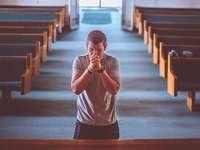 Gebet - Ein Mann, der in einer Kirche betet. Eine Person, die auf einer Bank sitzt.