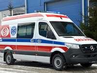 Sta arrivando un'ambulanza - Veicolo dell'ambulanza sul segnale Un camion bianco e blu rosso ha parcheggiato in un parche