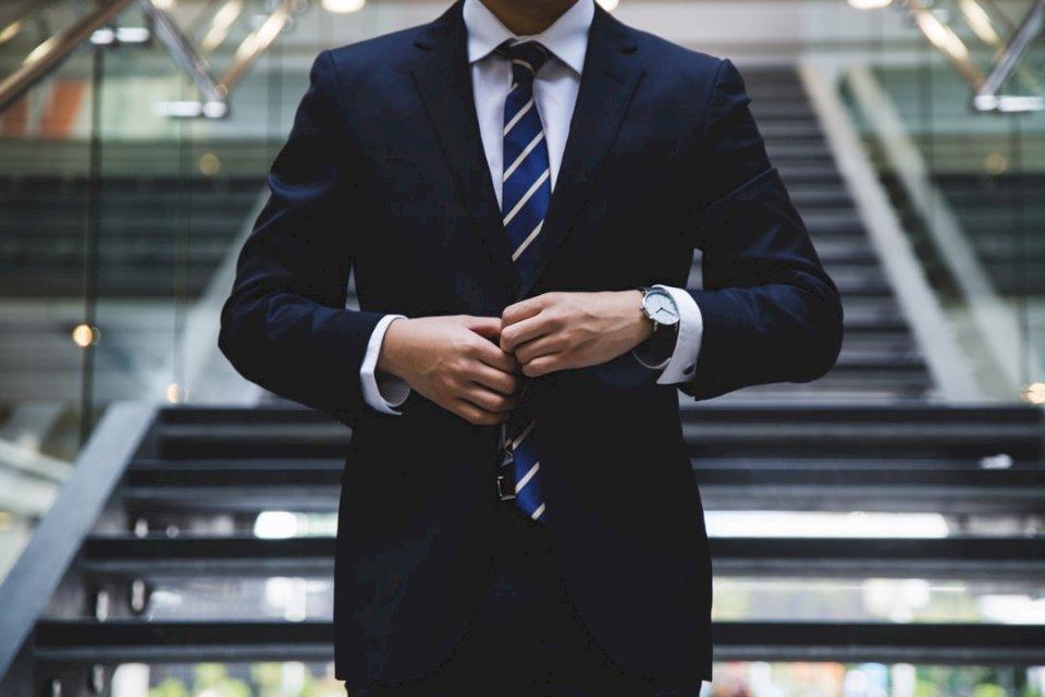 Questa è una foto del proprietario di - Persona in piedi vicino alle scale. Nuova Zelanda. Una persona che indossa giacca e cravatta.