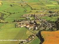 Családi kirakós játékok - Dalrymple Village, Skócia. Egy nagy zöld mező.