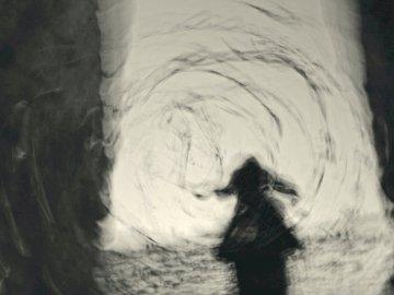 Cirkular Monokhrome-3 - Femme en robe noire debout devant un mur blanc. Une image floue d'une fille.