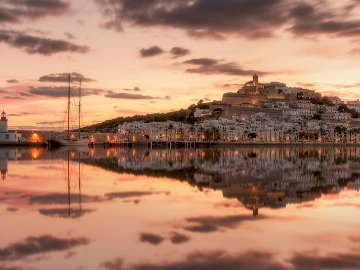 Ibiza views of the port - Ibiza views of the port. A sunset over a body of water with a city in the background.