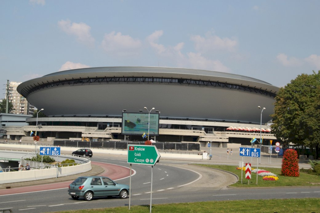 """Spodek in Katowice - Unterhaltungshalle """"Spodek"""" in Katowice. Ein Auto parkte am Straßenrand (4×5)"""