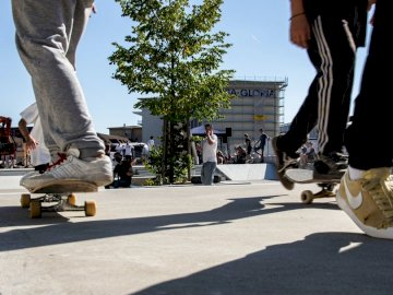 Many feet and skateboards - People skating on street during daytime. Switzerland. A man doing a trick on a skateboard.