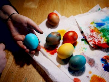 A lovely rustic rainbow of - Person holding red yellow and blue egg. New England, USA. A cake with fruit on top of a wooden table