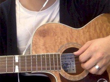 Hombre tocando la guitarra - joven tocando la guitarra. Una persona con una guitarra.
