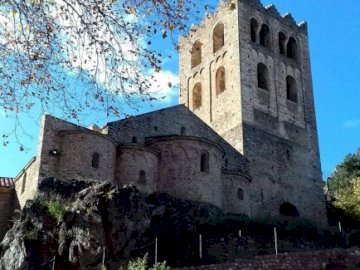 marie-do - Elne Cathedral near Perpignan in the eastern Pyrenees. A stone castle with a clock on the side of a