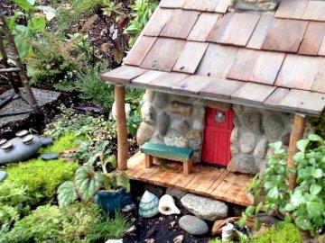 Una miniatura de la casa en el jardín. - Una miniatura de la casa en el jardín. Un banco de madera en un jardín.