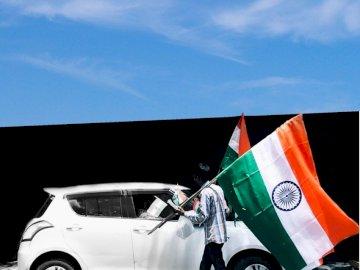 Ich glaube, unsere Flagge ist mehr - Mann, der Flagge von Indien neben weißem Auto hält. Ein Auto parkte am Straßenrand.