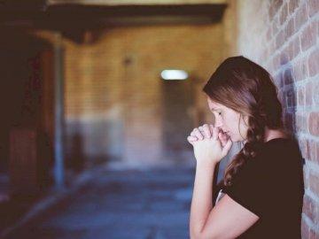 Femme en prière - Femme priant en s'appuyant contre le mur de briques. Michigan. Une femme debout devant un b�