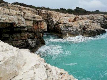 Cape Kamenjak - Kamenjak în Istria- Croația. O stâncă stâncoasă cu apă și un munte pe fundal.
