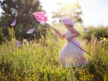 Persiguiendo mariposas - niña con un cazamariposas. Una niña volando una cometa en un campo.
