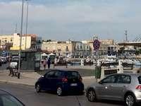 town - En liten stad vid Medelhavet. En bil som kör på en stadsgata fylld med mycket trafik.