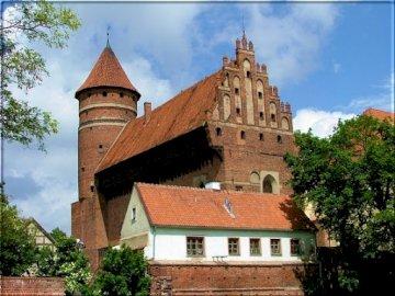 Zamek Olsztyn - Zamek w Olsztynie na Starym Mieście. Duży ceglany budynek z wieżą zegarową przed domem z katedr