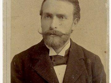 wyspianski_puzzle - Portret Stanisława Wyspiańskiego. Mężczyzna ubrany w garnitur i krawat pozuje do zdjęcia.
