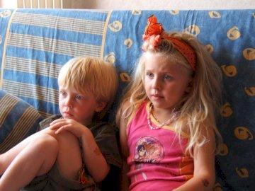 Lorna & Nathan - Ils regardent la télé à Rocquebrune. Une petite fille assise sur un canapé.