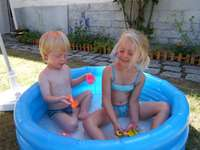 Lorna & Nathan - In the pool at Mamie Louise's. A little girl sitting in a plastic container.