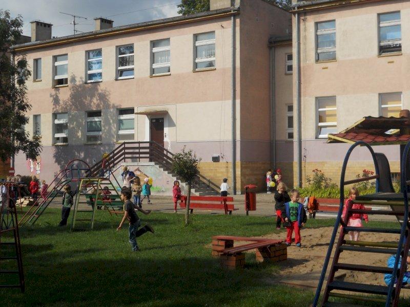 Koszalin - Kindergarten No. 34 Koszalin. Kindergarten No. 34 Koszalin. Un gruppo di persone su una panchina di fronte a un edificio (5×5)