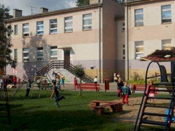 Koszalin - Przedszkole Nr 34 Koszalin. Grupa ludzi na ławce przed budynkiem.
