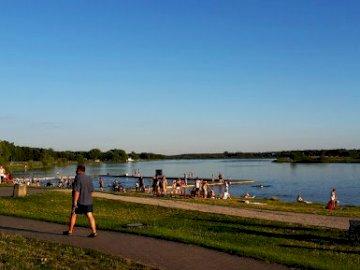 ¿Qué es este lugar? - Componga acertijos y descubrirá qué es este lugar. Un grupo de personas de pie junto a un lago.