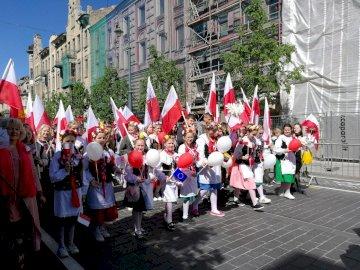 Pierwiosnki - Pierwiosnki podczas pochodu na Dzień Polonii. Grupa ludzi stojących przed tłumem.